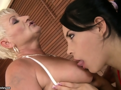 Old and youthful lesbian babes take a bubble bath and take up with the tongue some bald pussy